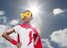 Muchacha en traje del super héroe con las manos en sus caderas contra el cielo en fondo Imagenes de archivo