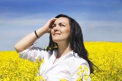 Muchacha en traje en el campo de flor amarillo foto de archivo