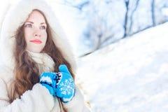 Muchacha en un abrigo de pieles blanco con los ojos azules contra un fondo de fotografía de archivo