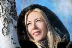 muchacha en un abrigo de pieles entre abedules Imágenes de archivo libres de regalías