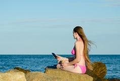 Muchacha en un bañador que se sienta en el teléfono con las piedras y el helado en las manos contra el mar Foto de archivo libre de regalías