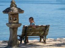 Muchacha en un banco en las orillas del mar foto de archivo