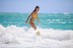 Muchacha en un bikiní amarillo que practica surf Imagenes de archivo