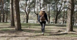 Muchacha en un bosque conífero en un día soleado en la primavera almacen de metraje de vídeo