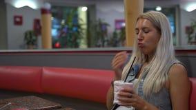 Muchacha en un café 4k de los alimentos de preparación rápida almacen de metraje de vídeo