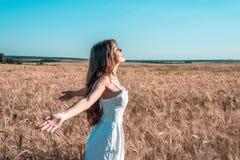 Muchacha en un campo blanco del vestido, reconstrucción al aire libre del trigo, vestido hermoso Las manos se abren en los lados  Fotografía de archivo