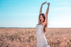 Muchacha en un campo blanco del vestido, reconstrucción al aire libre del trigo, vestido hermoso Mujer que presenta al aire libre Foto de archivo
