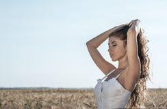 Muchacha en un campo blanco del vestido, reconstrucción al aire libre del trigo, vestido hermoso Una mujer está caminando al aire Imagen de archivo libre de regalías