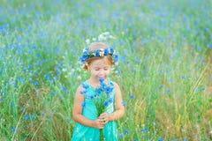 Muchacha en un campo que sostiene un ramo de flores azules Imagen de archivo libre de regalías