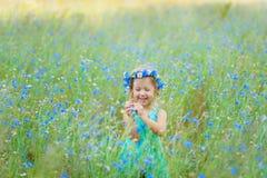 Muchacha en un campo que sostiene un ramo de flores azules Fotos de archivo