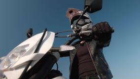 Muchacha en un casco de la motocicleta en una motocicleta almacen de metraje de vídeo