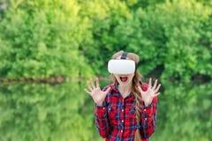 Muchacha en un casco de la realidad virtual en un fondo de la naturaleza fright fotos de archivo libres de regalías