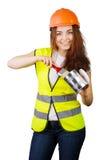 Muchacha en un casco y un chaleco que sostienen un cepillo y una poder del metal de pintura Imagen de archivo