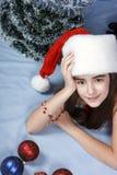 Muchacha en un casquillo con la Navidad Fotografía de archivo