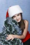 Muchacha en un casquillo con la Navidad Foto de archivo libre de regalías