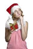 Muchacha en un casquillo de Papá Noel con el presente foto de archivo libre de regalías