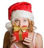 Muchacha en un casquillo de Papá Noel con el presente imagen de archivo