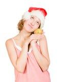 Muchacha en un casquillo de Papá Noel con la manzana de oro imagen de archivo libre de regalías