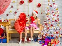 Muchacha en un casquillo y las manoplas de Santa Claus que se ríen de la muchacha que puso un saco en su cabeza Fotografía de archivo