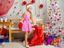 Muchacha en un casquillo y manoplas de Santa Claus con un bolso de los regalos de la Navidad Imagen de archivo