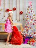 Muchacha en un casquillo y manoplas de Santa Claus con un bolso de los regalos de la Navidad Imagenes de archivo