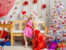 Muchacha en un casquillo y manoplas del baile de Santa Claus alrededor del bolso con los regalos de la Navidad Foto de archivo
