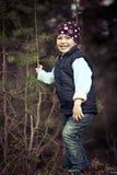 Muchacha en un chaleco que ríe en las maderas Fotografía de archivo
