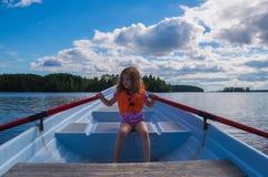 Muchacha en un chaleco salvavidas, niño en un barco, remando los remos Fotos de archivo