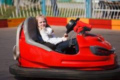 Muchacha en un coche de parachoques Imagenes de archivo
