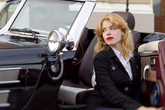 Muchacha en un coche viejo Foto de archivo libre de regalías