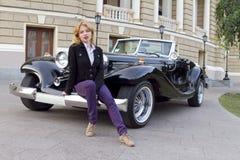 Muchacha en un coche viejo Foto de archivo