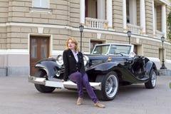 Muchacha en un coche viejo Imagen de archivo