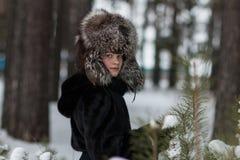 Muchacha en un día escarchado del invierno del sombrero de piel que camina en el bosque Fotografía de archivo