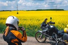 Muchacha en un equipo y vidrios de la protecci?n con la motocicleta tur?stica Campo de flores amarillo Viaje, enduro y apagado ca foto de archivo