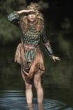 Muchacha en un estilo inusual de la moda que se coloca en agua fotografía de archivo