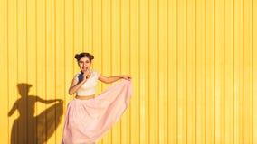 Muchacha en un fondo amarillo de la pared Foto de archivo