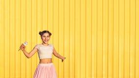 Muchacha en un fondo amarillo de la pared Imágenes de archivo libres de regalías
