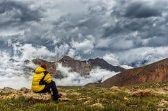 Muchacha en un fondo de las montañas, nubes, sentándose en una piedra Foto de archivo libre de regalías