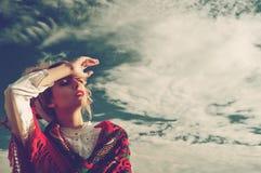 Muchacha en un fondo del cielo azul Imagen de archivo libre de regalías