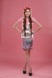 Muchacha en un fondo rosado con la guirnalda Imagen de archivo