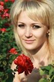 Muchacha en un jardín de rosas rojas Fotos de archivo