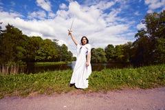 Muchacha en un juego blanco con un capo motor de la fantasía Fotos de archivo libres de regalías