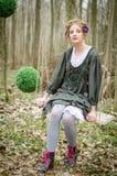 Muchacha en un oscilación en el bosque Fotos de archivo libres de regalías