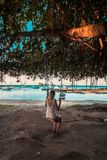 Muchacha en un oscilación en la playa del malheureux del casquillo, Mauricio foto de archivo