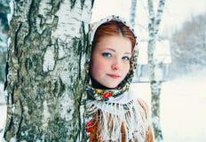 Muchacha en un pañuelo en los abedules en invierno Imágenes de archivo libres de regalías