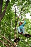 Muchacha en un parque de la actividad de la aventura que sube Imágenes de archivo libres de regalías