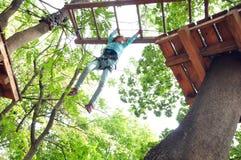 Muchacha en un parque de la actividad de la aventura que sube Foto de archivo libre de regalías