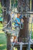 Muchacha en un parque de la aventura que sube Foto de archivo