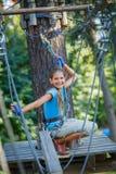 Muchacha en un parque de la aventura que sube Imagenes de archivo