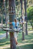 Muchacha en un parque de la aventura que sube Fotos de archivo